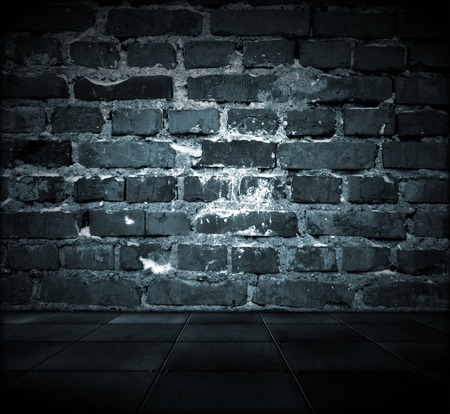 A dark grungy room with a cracked brick wall and tiled floor photo