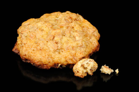 Oatmeal Cookie with Crumbs on Black Background photo