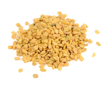 A pile of fenugreek seeds isolated on a white background