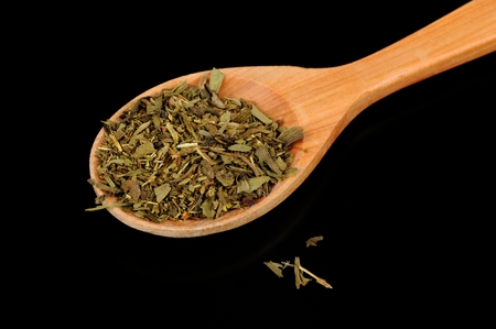 herbs de provence: A pile of dried herbes de Provence (a mixture of dried herbs typical of Provence) in a wooden spoon against a black