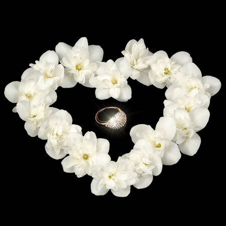 Diamond Ring in Heart Made of White Jasmine Flowers on Black Background photo