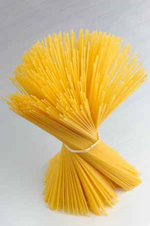 Raw Whole-Wheat Spaghetti Pasta on Metal Background
