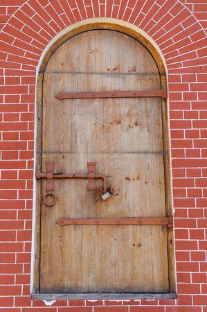Vintage round top front door with latch in brick wall Imagens