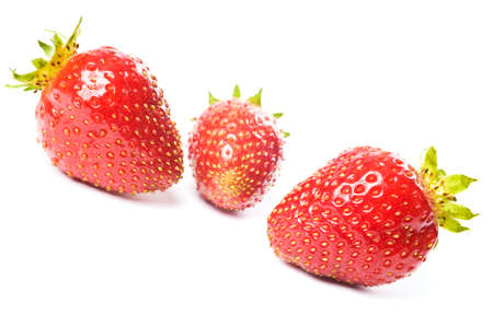 Three fresh ripe red strawberries, isolated on white with soft shadow. Studio shot.