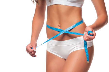 Weight loss - woman with trained belly. Young skinny female in white panties with tanned body is measuring her waist with blue tape measure and showing diet results. Studio shot, white background.
