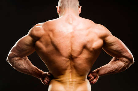 Body Builder Posing - Rear Lat Spread. Strong healthy power fitness handsome athletic man with muscular trained body flexing his lateral back muscle on black background.