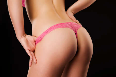 Beautiful slim female body. Close-up photo of ideal elastic flawless woman's ass wearing pink lace panties. Taut elastic ass. Firm sexy buttocks. Isolated on black background.
