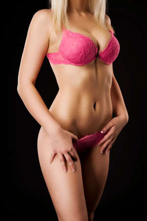 Beautiful slim female body. Close-up photo of ideal elastic flawless woman's belly wearing pink lace underwear. Taut elastic legs. Firm sexy breast. Isolated on black background. Imagens