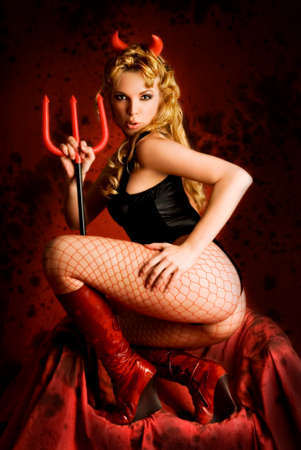 Temptating devil girl in hell. Sexy young blond satanic woman with horns and trident showing off her buttocks on dark red throne. Standard-Bild