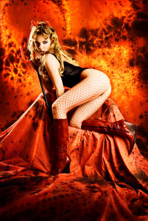 Temptating devil girl in hell. Sexy young blond infernal woman with horns and trident and fire lava in background showing off her buttocks on dark red throne.