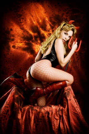 Temptating devil girl in hell. Sexy young blond satanic woman with horns and trident, fire wings on background showing off her buttocks on dark red throne.