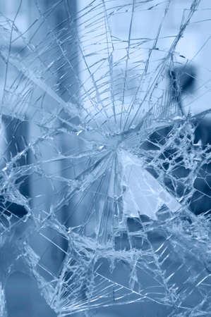 Accident - close-up of broken window. Detail of rifts of cracked glass. Blue background. Foto de archivo