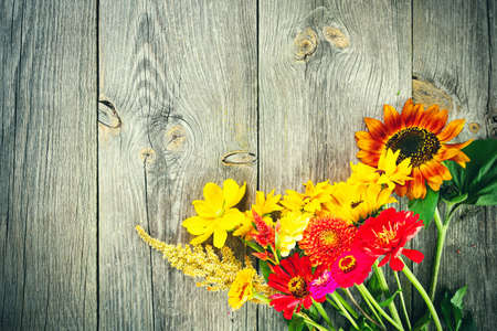 Holiday autumn bouquet. Frame of colorful flowers arranged on old wooden background. Top view and copy space for your advertising text message or promotional content.