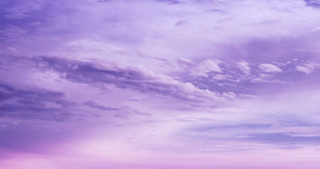 Beautiful purple sky background. Soft white clouds at sunset. Many pink and magenta tones and patterns of clouds.