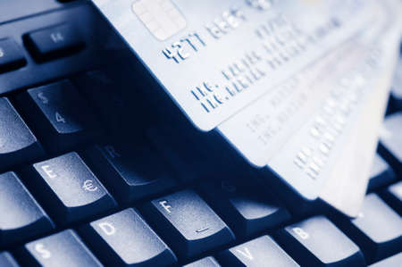 Four credit cards on blue computer keyboard. E-commerce data and ebanking protection, internet and finance security concept. Stock Photo