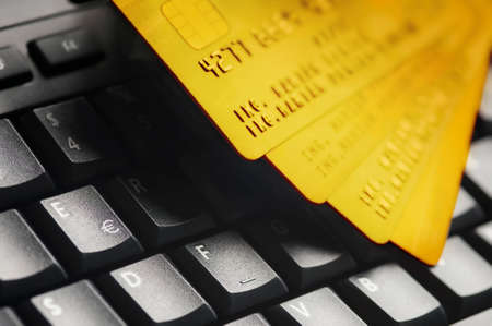 Four golden credit cards on black computer keyboard.  E-commerce data and ebanking protection, internet and finance security concept.