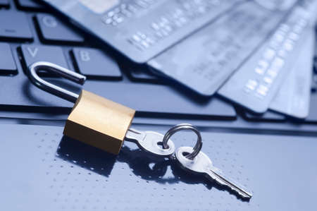 Unlocked padlock, keys and four credit cards on blue computer keyboard. E-commerce data and ebanking protection, internet and finance security concept.