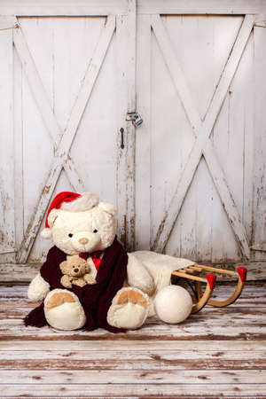 Two teddy bears with Christmas hats on wooden gate background, vintage filter Stock Photo