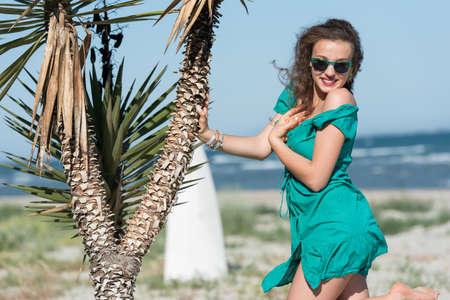 siervo: Mujer con el pelo largo y rizado usar un vestido corto apoyado en palmeras. Cielo y el mar como fondo Foto de archivo