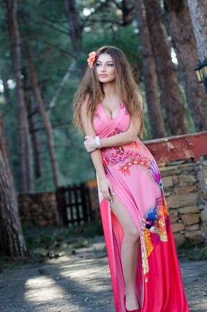 attach         â     â       ©: jovencita preciosa que llevaba elegante vestido de pie durante mucho tiempo entre los árboles