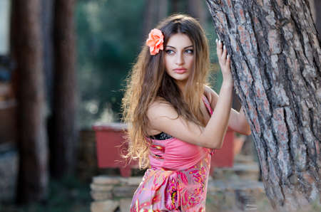 Lovely young lady wearing elegant long dress standing among the trees
