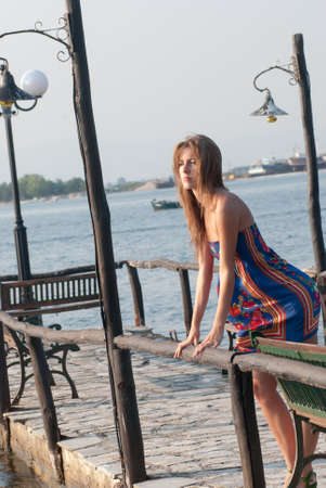 Young blond fashion woman standing on a small old harbor Stock Photo