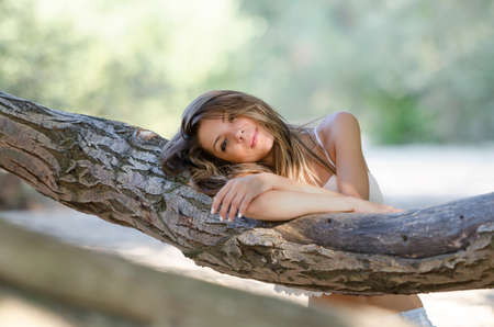 leaning against: Nostalgic moments of a beautiful girl as she rests on a tree trunk