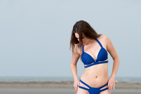tall woman: Tall woman with long red hair wear bikini and pose on the sand Stock Photo