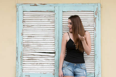 decollete: Tall woman standing against old wooden window, wearing shorts and decollete black shirt