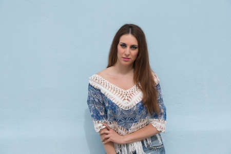 leaning against: Woman leaning against blue wall wearing shorts and crochet shirt