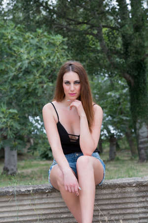 decollete: Woman sitting on cement short wall, wearing shorts and decollete black shirt Stock Photo