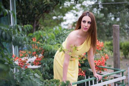Junge Dame auf dem Balkon stehen. Suurounding mit orangen Blüten und gelben langen Kleid tragen