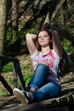 Young woman sitting on wooden bridge in the forest Stock Photo