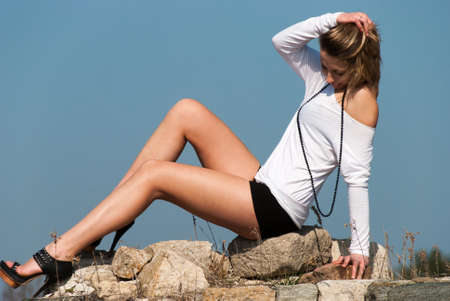emphasise: Female model reclining on rocks, emphasize her long legs