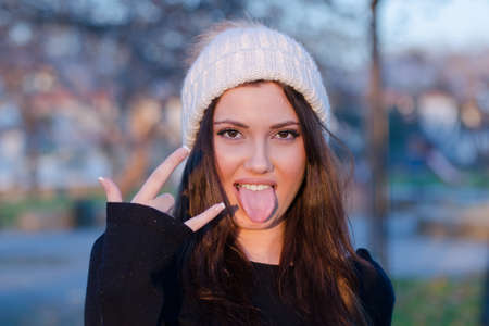Face of a lovely woman wear winter knitted cap sticking out tongue making a rock finger symbol