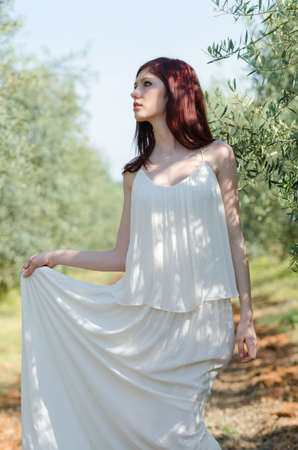 Portrait of a girl with white long dress in the olive grove