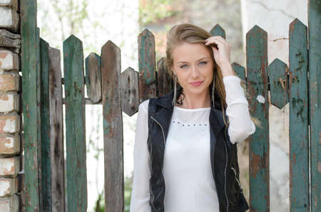 Sweet blond woman is leaning against a fence Stock Photo