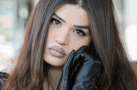 Woman with a unique fleshy lips wearing leather jacket facing the camera, photo taken through the glass