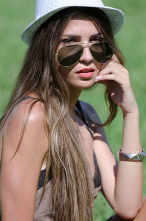 Beautiful girl on grass with hat and sunglasses on bright sunny day