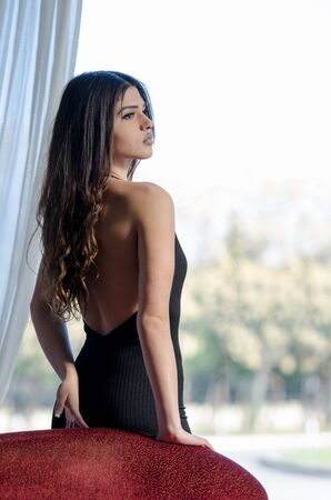 Beautiful woman with juicy lips and long brunette hair, wearing strap low open back elegant long jumper playsuit romper, pose front of a glass partition Stock Photo