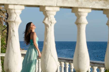 beachfront: Beautiful lady standing on veranda of a beachfront home, ocean as background