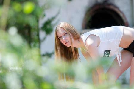 Slim blonde with white short printed shirt at backyard