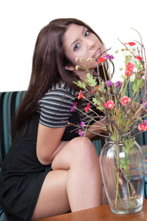 divan: Lady sitting in living room , front of her there is a vase with flowers Foto de archivo