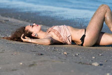 wet t shirt: Woman with long curly hair wear bottom bikini, sunglasses and wear spaghetti strap, lying on the beach. Sea as background Stock Photo