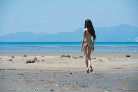 depart: Slim girl wear bikini and walking on a long land of sand, horizontal and full body length photo