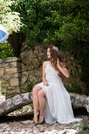 Beautiful girl with curly hair wear long white dress like a bride, sitting on a small rock bridge Stock Photo