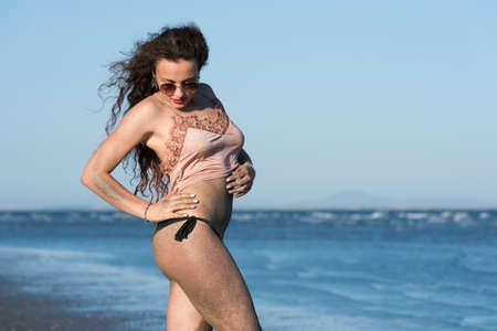 wet t shirt: Woman with long curly hair wear bottom bikini, sunglasses and wear spaghetti strap, on the beach. Sea and sky as background