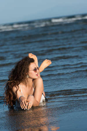 Woman with long curly hair wear bottom bikini, sunglasses and white shirt, lying in sea water Stock Photo
