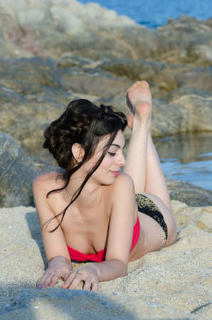 Young slim pretty lady wear red and black bikini lying prone on sand, sea and rocks as background Stock Photo