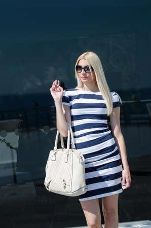 Beautiful fashion blonde woman presenting a white handbag